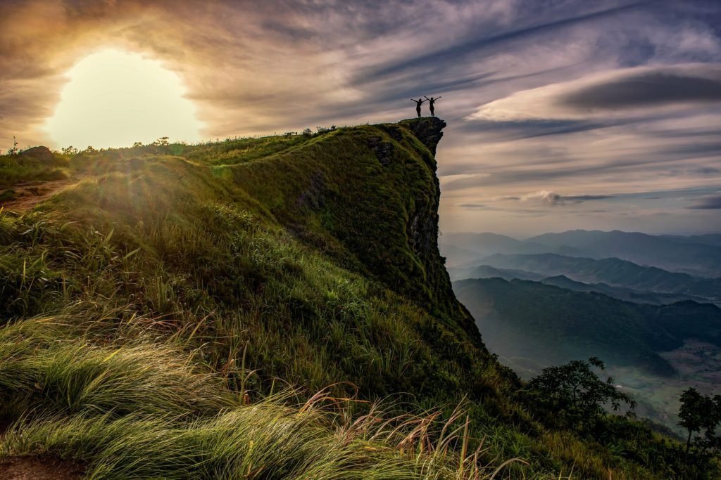 Photo of a green cliff in sunlight with two people at the tip